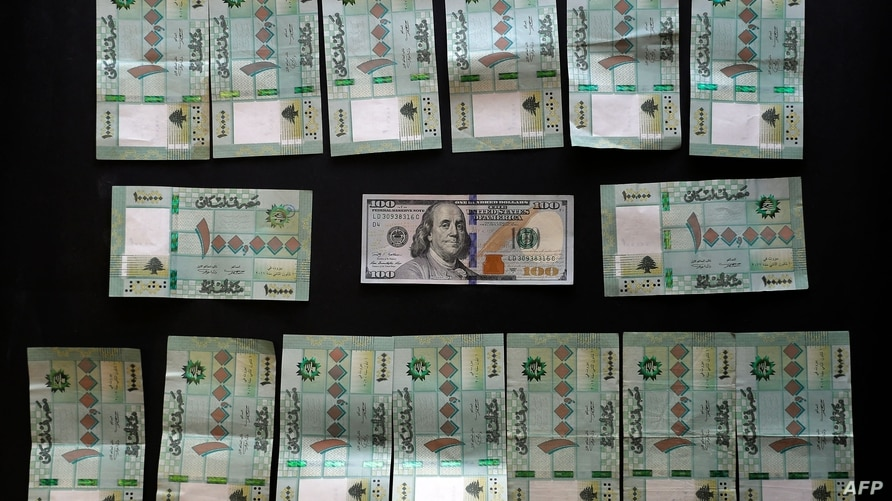 A picture shows the value in Lebanese pounds of a 100 US Dollar bill on the black market exchange rate (1,500,000 LP) in Beirut…