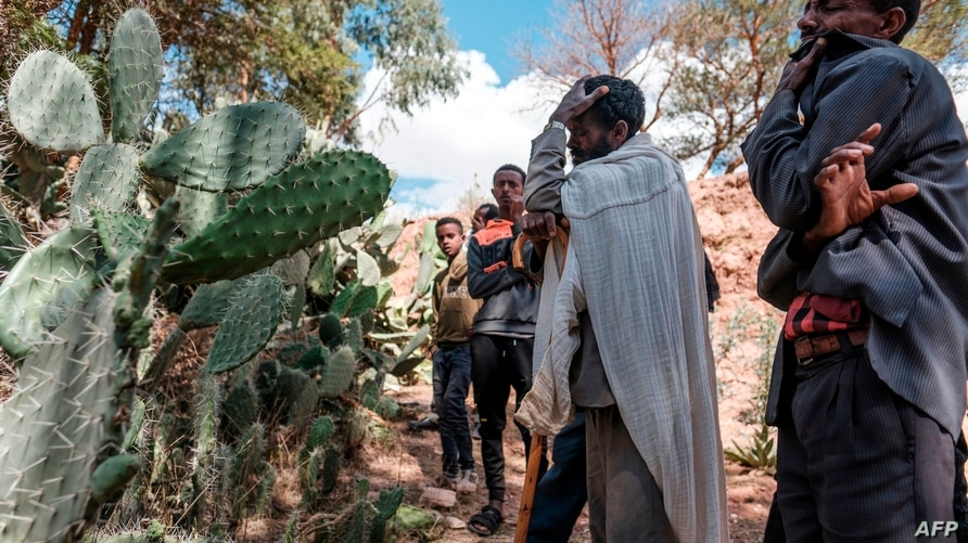 People mourn in front of a mass grave the victims of a massacre allegedly perpetrated by neighbouring Eritrean Soldiers in the…