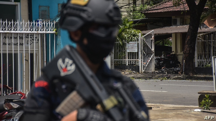 An Indonesian policeman stands guard at the site of an explosion outside a church in Makassar on March 28, 2021. (Photo by…