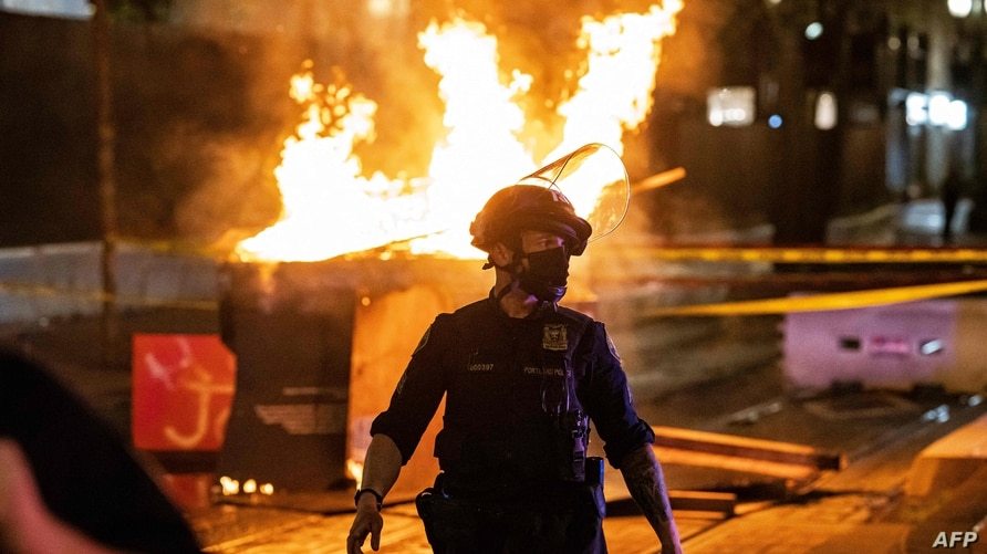 PORTLAND, OR - APRIL 17: Portland Police responds to a structure fire, set by protesters following the police shooting of a…
