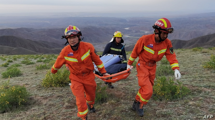 This photo taken on May 22, 2021 shows rescuers carrying equipment as they search for runners who were competing in a 100…