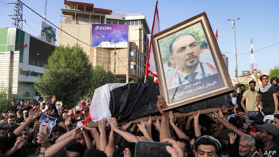 People chant slogans as they march with the body of renowned Iraqi anti-government activist Ihab al-Wazni (Ehab al-Ouazni)…