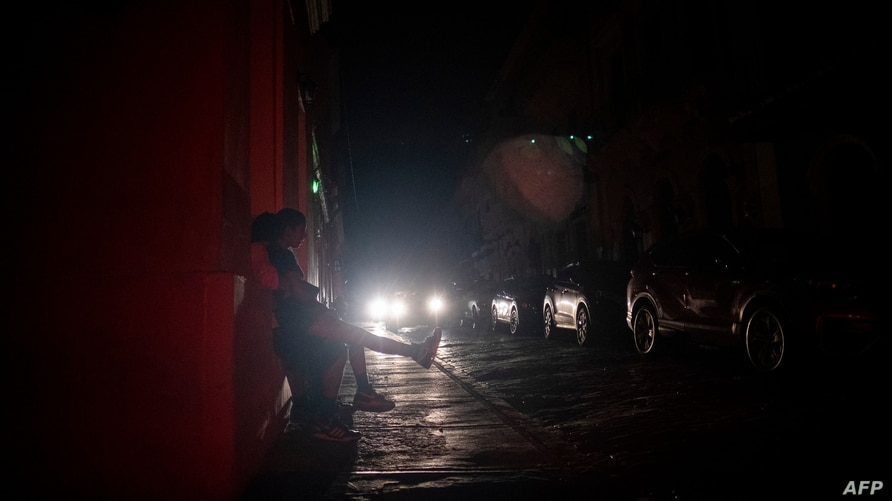 People sit on the sidewalk of a street left in darkness by a power outage due to a cyberattack in Old San Juan, Puerto Rico,…