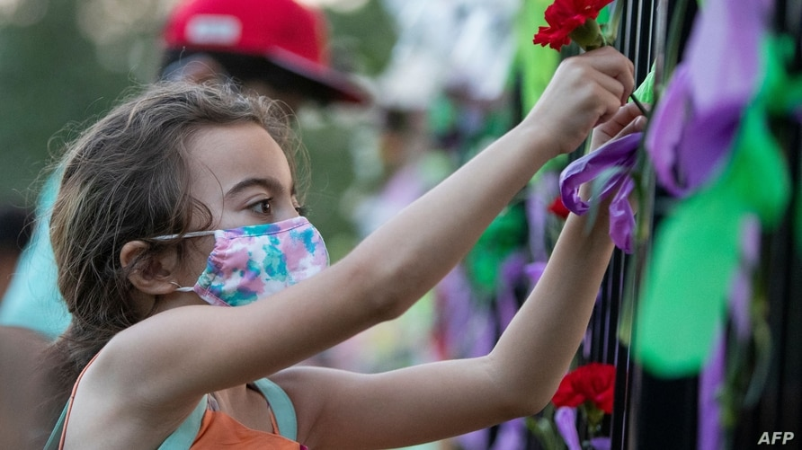 A young girl puts a flower on the fence of the London Muslim Mosque during the multi-faith march to end hatred, after a man…
