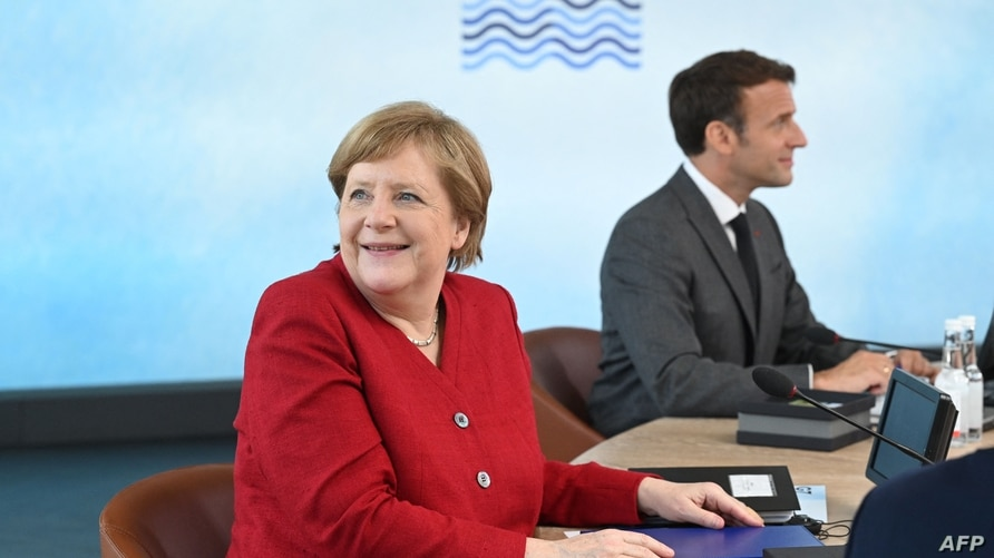 Germany's Chancellor Angela Merkel (L) and France's President Emmanuel Macron sit around the table at the start of the G7…