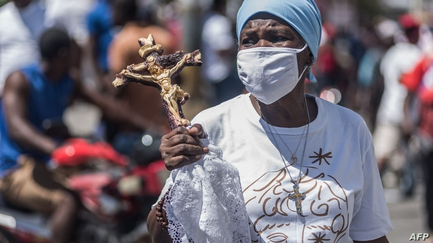 (FILES) In this file photo Haitian protesters march through the streets on February 28, 2021 in Port-au-Prince, to denounce the…