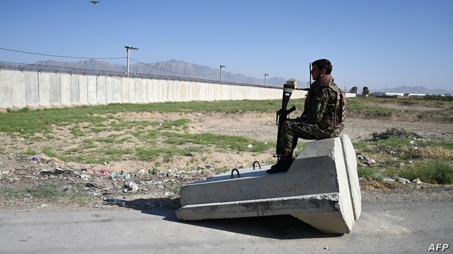 TOPSHOT - An Afghan National Army (ANA) soldier sits at a road checkpoint near the a US military base in Bagram, some 50 km…