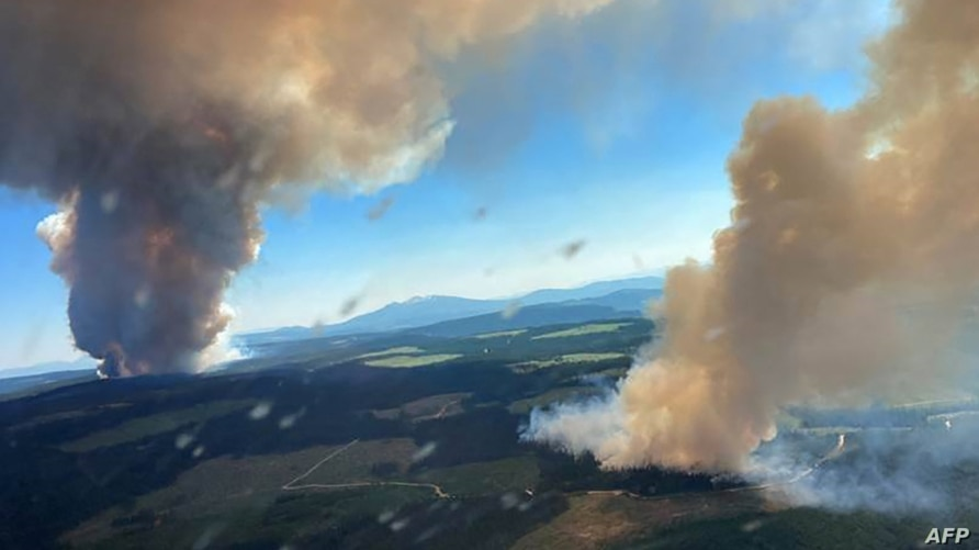 (FILES) This file handout photo courtesy of BC Wildfire Service shows two plumes of smoke from the Long Loch wildfire (K51040)…
