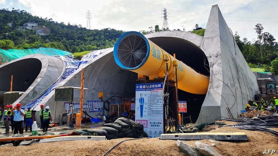 Rescuers work to clear a flooded tunnel after 14 construction workers were trapped in an underground section of a new highway…
