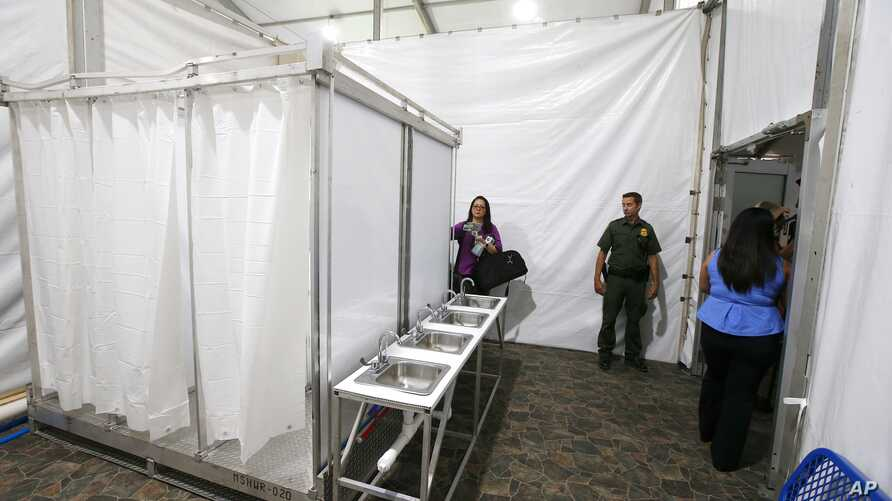 Shower stalls and sinks are seen as the U.S. Border Patrol unveiled a new 500-person tent facility, June 28, 2019, in Yuma,  Arizona.