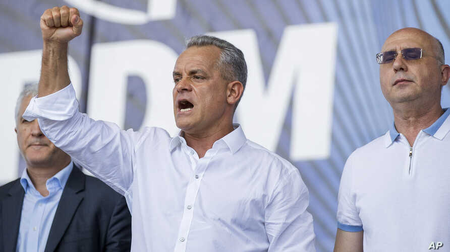 Vladimir Plahotniuc, the leader of the Moldova's Democratic party, and the country's de facto leader, gestures as he addresses a rally, next to interim president Pavel Filip, right, in Chisinau, Moldova, June 9, 2019.