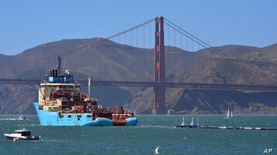 FILE - In this Sept. 8, 2018 photo, a ship tows The Ocean Cleanup's buoyant trash-collecting device toward the Golden Gate Bridge en route to the Pacific Ocean. The floating device is designed to catch plastic waste.
