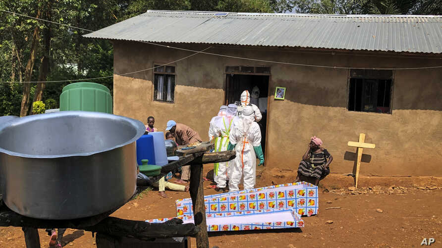 Ebola workers enter a house to decontaminate the body of a woman suspected of dying from Ebola, before the vehicle of the health ministry Ebola response team was attacked in Beni, northeastern Congo Monday, June 24, 2019. A driver working with the…