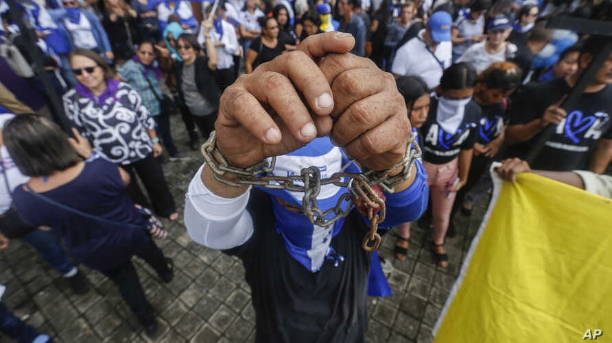 A man holds up his chained wrists during a memorial on the one year anniversary of a government crackdown on a Mother's Day march, outside the Catedral in Managua, Nicaragua, Thursday, May 30, 2019. An international fact-finding group last year said…