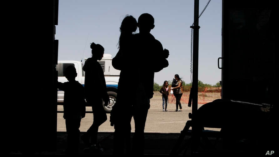 FILE - Migrants, mainly from Central America, guide their children into a World War II-era bomber hanger in Deming, N.M. A panel of appeals court judges in California will hear arguments over conditions in detention and holding facilities near the border.