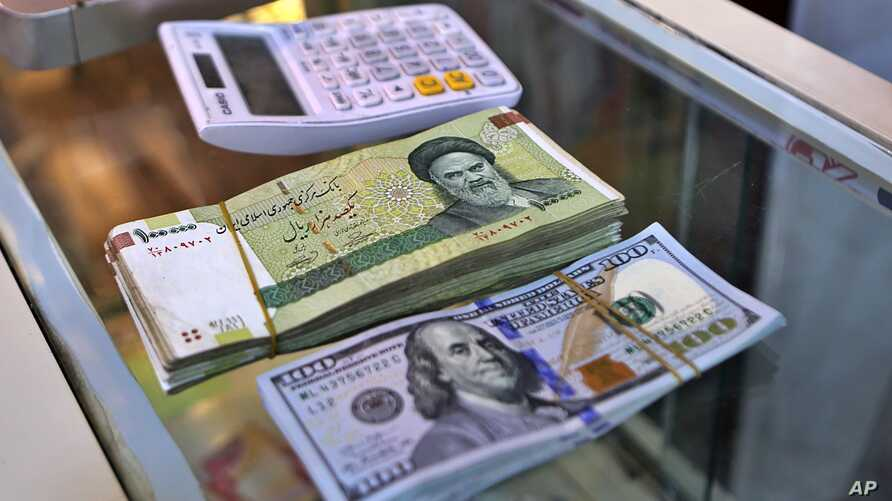 In this Wednesday, May 21, 2019, photo, U.S. and Iranian currency are readied by a money exchanger outside the golden-domed shrine of Imam Moussa al-Kadhim in Kadhimiya district in north Baghdad, Iraq.