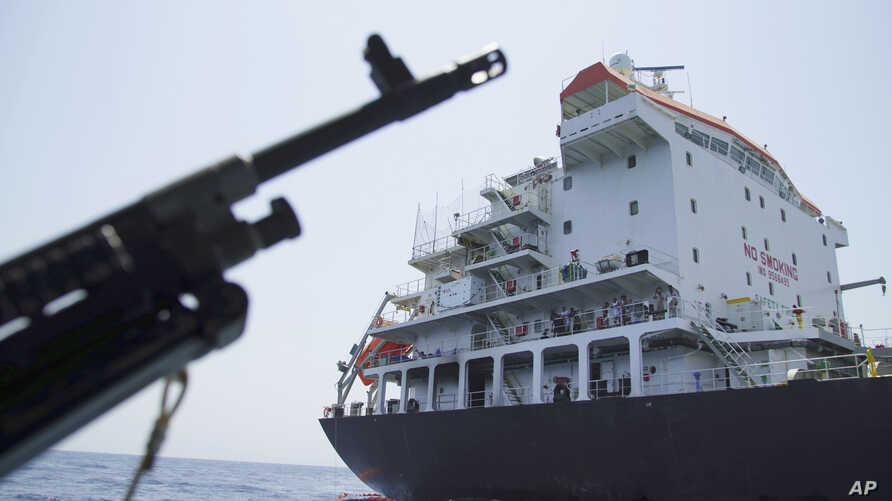 Sailors stand on deck above a hole the U.S. Navy says was made by a limpet mine on the damaged Panama-flagged, Japanese owned oil tanker Kokuka Courageous, anchored off Fujairah, United Arab Emirates.  during a trip organized by the Navy for journalists, June 19, 2019.