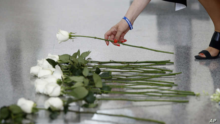 Andrea Chamblee, widow of Capital Gazette journalist John McNamara, places a flower at the foot of the Newseum's Journalists Memorial in Washington, Monday, June 3, 2019.