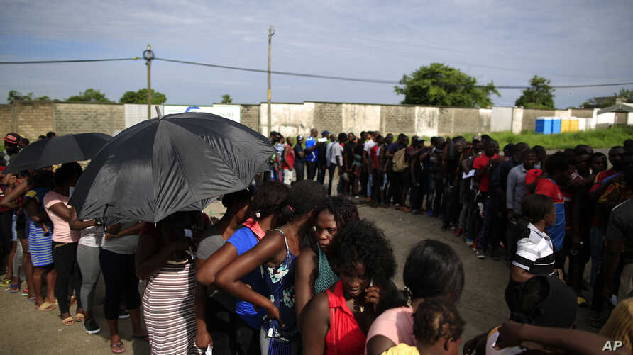 Mainly Haitian along with some African migrants wait in men's and women's lines to request documents giving them temporary legal status in Mexico, outside the Siglo XXI detention center in Tapachula, Mexico, Wednesday, June 12, 2019.