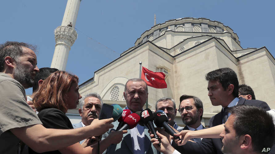 Turkish President Recep Tayyip Erdogan speaks to the media after Friday prayers, in Istanbul, Friday, June 7, 2019. Erdogan says his country is determined to protect Turkish Cypriots' rights to gas deposits in the eastern Mediterranean.