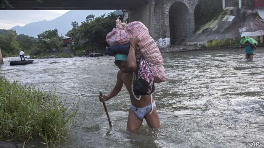 Men carry loads of supplies as they cross the Suchiate river from Guatemala into Talisman, Mexico,  June 21, 2019. Mexico's foreign minister says that the country has completed its deployment of some 6,000 National Guard members to help.