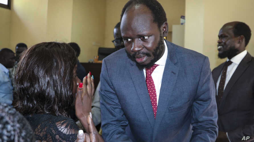 Prominent South Sudanese activist and economist Peter Biar Ajak prepares to embrace his wife Nyathon Hoth Mai, left, as she weeps after he was sentenced to two years in prison, in a courtroom in the capital Juba, South Sudan Tuesday, June 11, 2019…