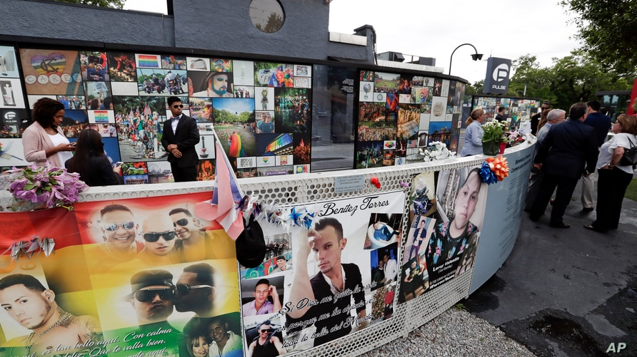 People gather at the Pulse nightclub before a news conference to introduce legislation that would designate the site as a national memorial, Monday, June 10, 2019, in Orlando, Fla. (AP Photo/John Raoux)