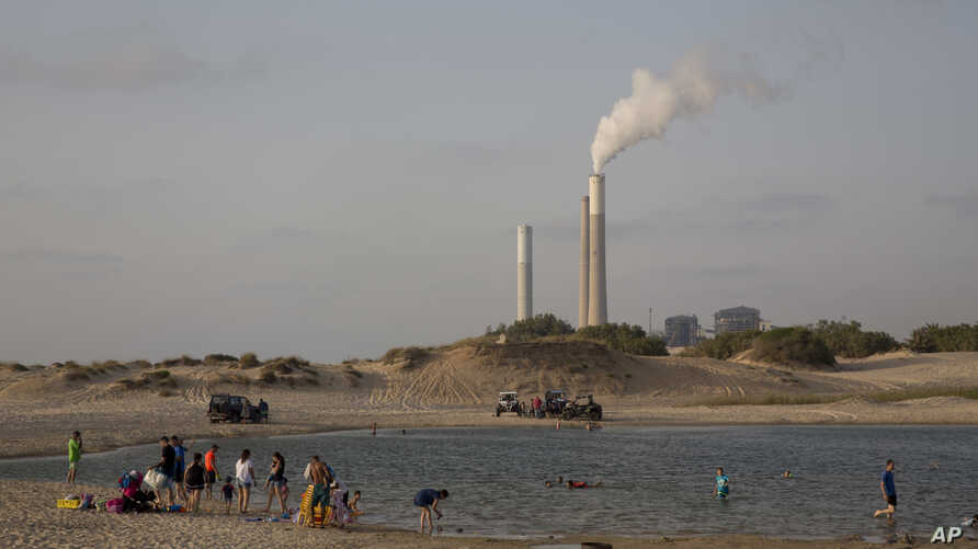 FILE - Israel's electricity power plant in Ashkelon is seen as people bath near kibbutz Zikim, on the Israel Gaza Border,  June 19, 2017.