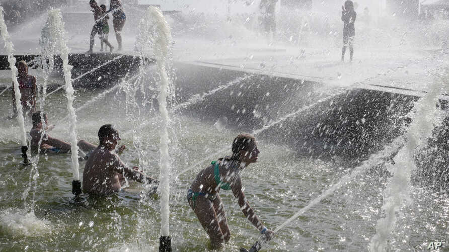 People bathe at a fountain escaping the heat wave, in St.Petersburg, Russia, Saturday, July 27, 2019. (AP Photo/Dmitri Lovetsky)