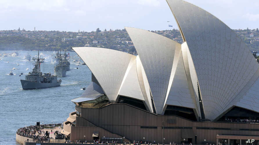 FILE - In this Oct. 4, 2013, file photo, the Opera House is seen as Australian warships from front, HMAS Sydney, Darwin and Perth enter the harbour in Sydney, Australia, during the International Fleet review.  Minister for Cities, Urban…