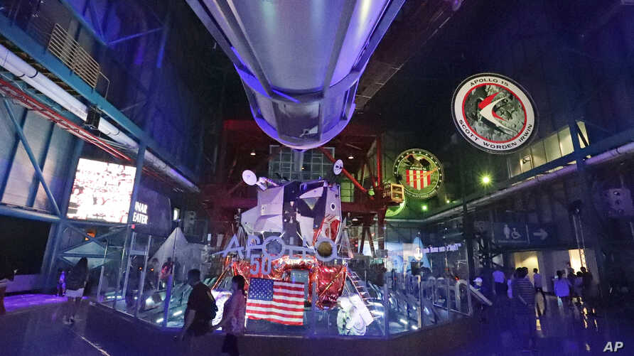 Guests pass by an exhibit under the nose of a Saturn V rocket at the Kennedy Space Center Visitor Complex Thursday, July 18, 2019, in Cape Canaveral, Fla., during celebrations for the 50th anniversary of the Apollo 11 moon landing. (AP Photo/John…