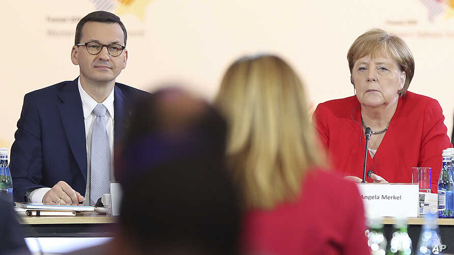 German Chancellor Angela Merkel,right, and Poland's Prime Minister Mateusz Morawiecki listening to a speech by Poland's President Andrzej Duda during a summit meeting that aims to reassure Western Balkan states that their aspirations to join the…
