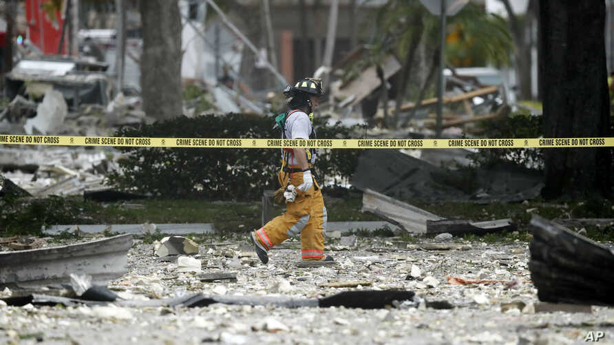 A firefighter walks through the remains of a building after an explosion, July 6, 2019, in Plantation, Fla.