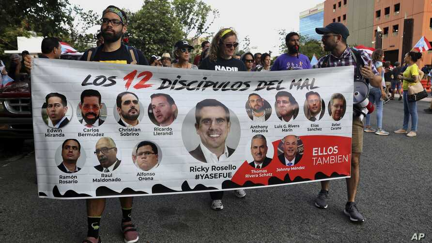 "Protesters hold a banner featuring resigned Gov. Ricardo Rosselló, center, amid other politicians that reads ""The 12 disciples of evil. Them too."" as they demand the resignation of Justice Secretary Wanda Vazquez in San Juan, Puerto Rico, July 29, 2019."