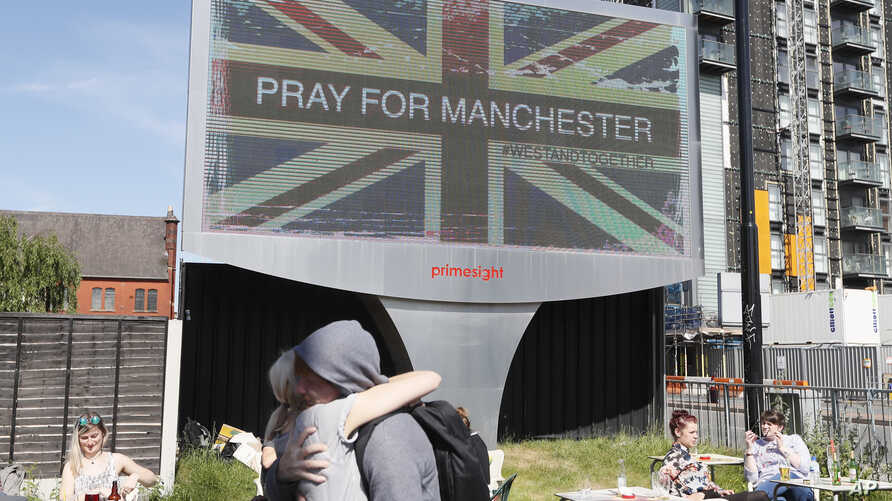 FILE - In this Tuesday May 23, 2017 file photo, couple embrace under a billboard in Manchester, England, the day after the suicide attack at an Ariana Grande concert that left more than 20 people dead.