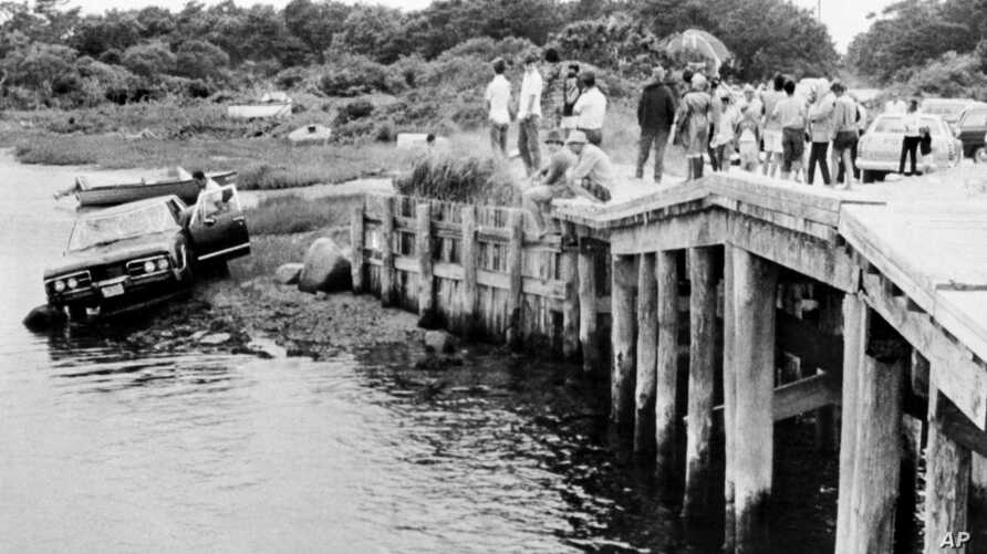 FILE - In this July 19, 1969 file photograph, crowds watch as U.S. Sen. Edward Kennedy's car is pulled from water at the Dyke Bridge in Edgartown, Mass. It's been 50 years since the fateful automobile accident that killed a woman and thwarted…