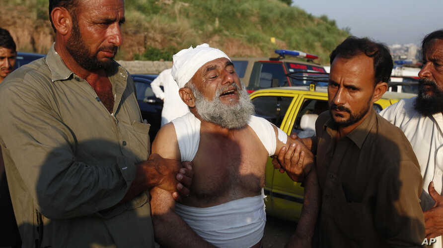 People help an injured victim who morns for the lost of his family member at the site of plane crash in Rawalpindi, Pakistan, Tuesday, July 30, 2019. A small Pakistani military plane crashed into a residential area near the garrison city of…