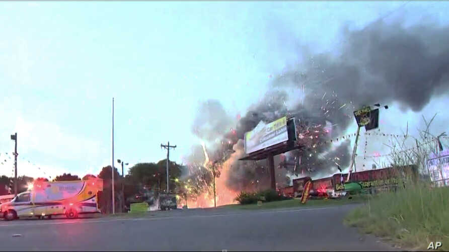 This still image taken from video provided by WCNC shows containers of fireworks exploding at the Davey Jones Fireworks and the House of Fireworks stores in Fort Mill, S.C., on Thursday, July 4, 2019.   Firefighters had to dodge exploding rockets to…