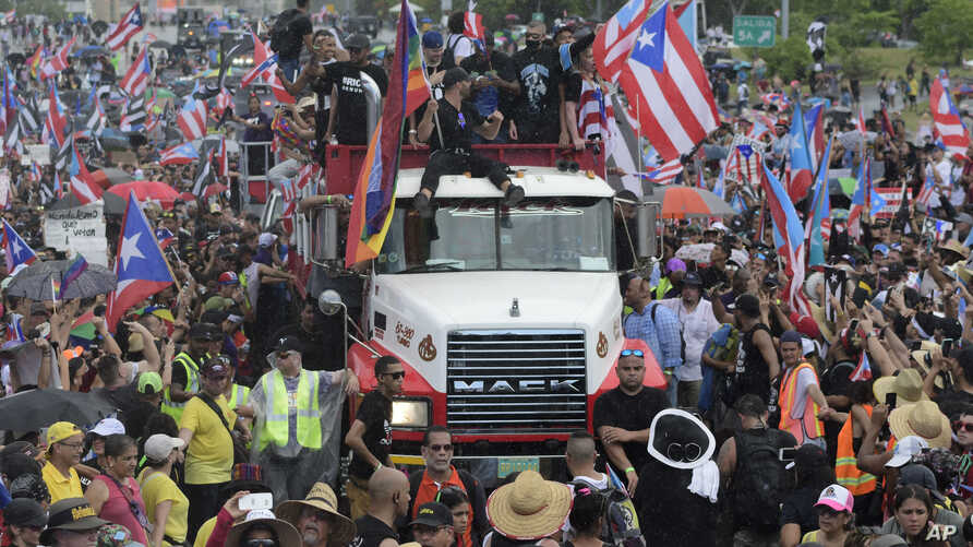 Puerto Rican singer Ricky Martin, front atop truck, participates with other local celebrities in a protest demanding the resignation of governor Ricardo Rossello in San Juan, Puerto Rico, Monday, July 22, 2019. Protesters are demanding Rossello step…