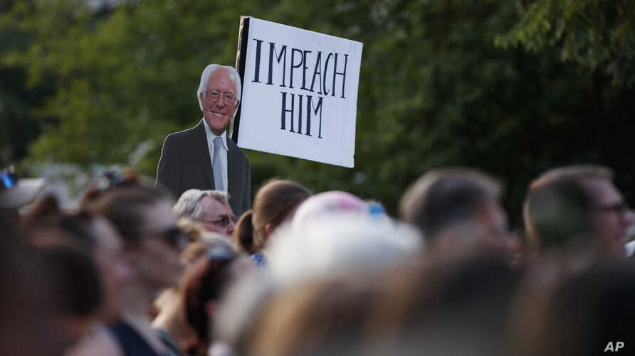 A sign of Democratic presidential candidate Sen. Bernie Sanders, I-Vt., with 'Impeach Him' is held high during a protest by Washington area national and local organizations including CASA, Center for Popular Democracy, Faith in Action, and the…