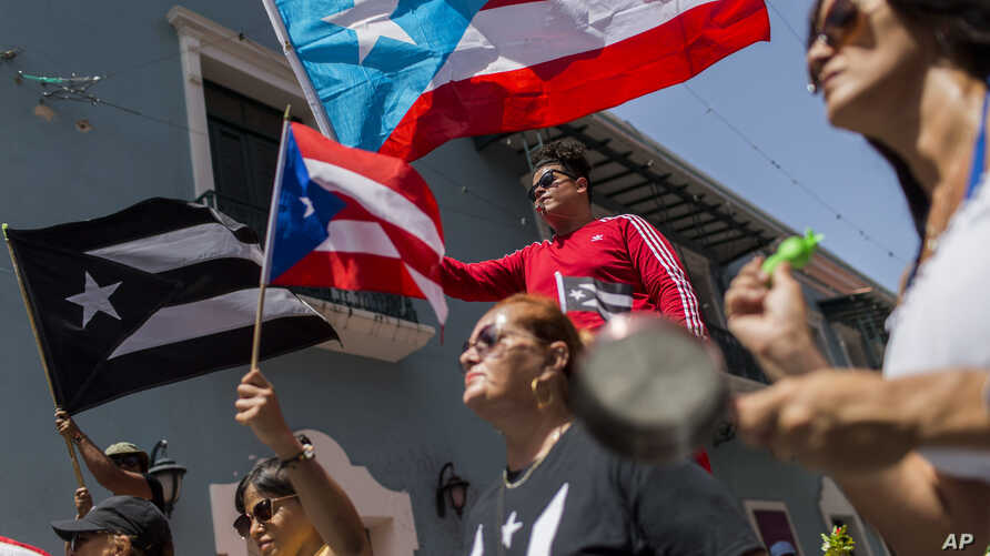 Demonstrators, some waving Puerto Rican national flags, gather in front of the governor's mansion La Fortaleza, in San Juan, Puerto Rico, July 24, 2019.