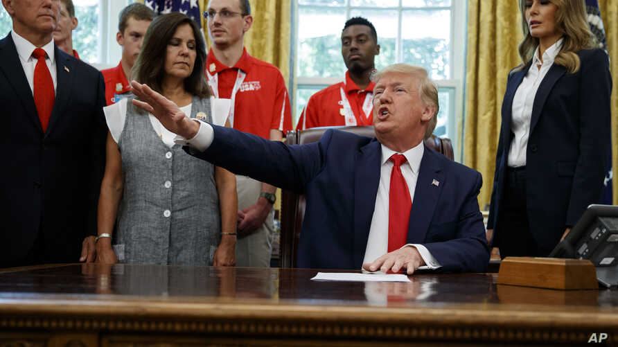President Donald Trump, accompanied by Vice President Mike Pence, Karen Pence, and first lady Melania Trump, speaks during a photo opportunity with members of the 2019 U.S. Special Olympics athletes and staff, in the Oval Office of the White House,…