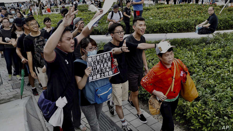 "Protesters walk behind a mainland Chinese tourists, holding a card with their demands including ""Withdrawal of extradition bill"" and ""Real elections"" during a march in Hong Kong, July 7, 2019."