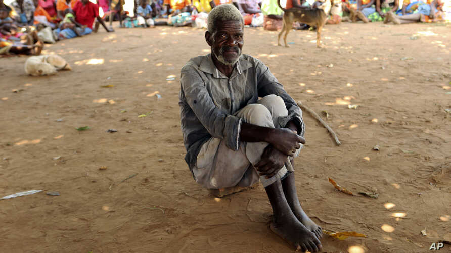A man waits to receive food aid outside a camp for displaced survivors of cyclone Idai in Dombe,  Mozambique,  April 4, 2019.