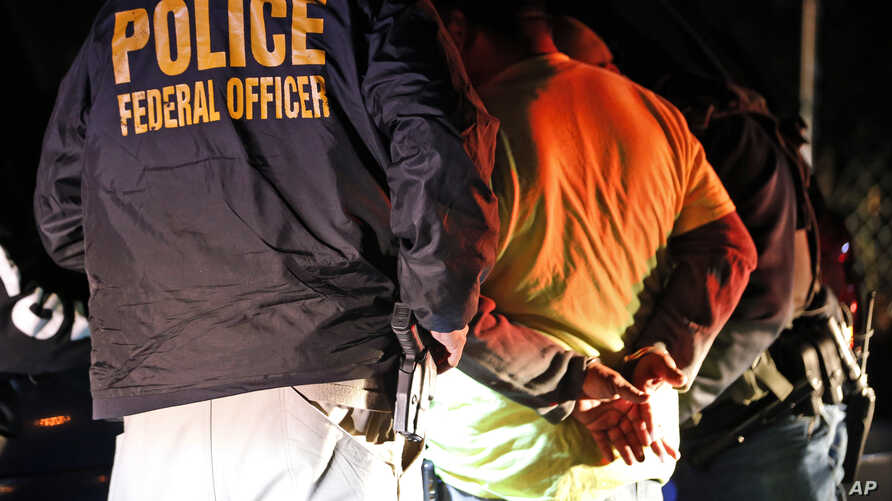 U.S. Immigration and Customs Enforcement agents surround and detain a person during a raid in Richmond, Va., Oct, 22, 2018.