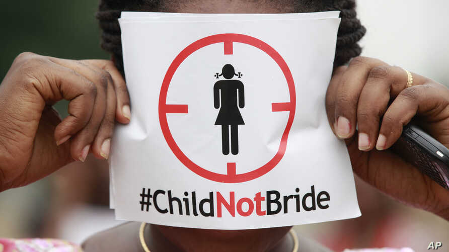 FILE- In this July 20, 2013, file photo, a woman protests against underage marriage in Lagos, Nigeria.