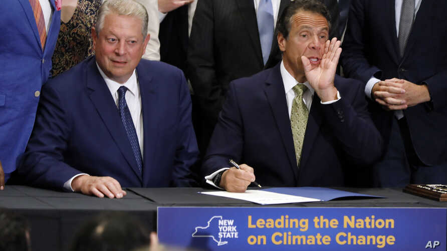 New York Gov. Andrew Cuomo, right, accompanied by former Vice President Al Gore, announces that he is signing the Climate Leadership and Community Protection Act, Thursday, July 18, 2019, at Fordham University in New York. New York's new law aimed…