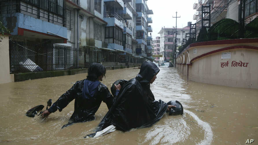 A Nepalese pulls his motorbike and wades past a flooded street in Kathmandu, Nepal, Friday, July 12, 2019. Heavy rainfall since Thursday night has caused havoc throughout the country. According to the meteorological department, rainfall across the…