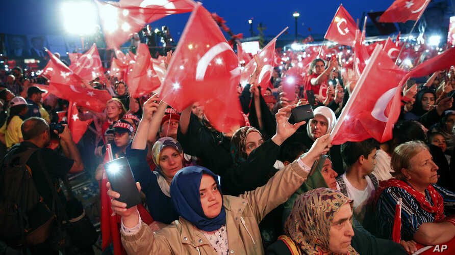 People wave Turkish flags as they listen to Turkey's President Recep Tayyip Erdogan during a rally to honor the victims of the July 15, 2016 failed coup attempt, part of the ceremonies for the three-year anniversary, in Istanbul,  July 15, 2019.