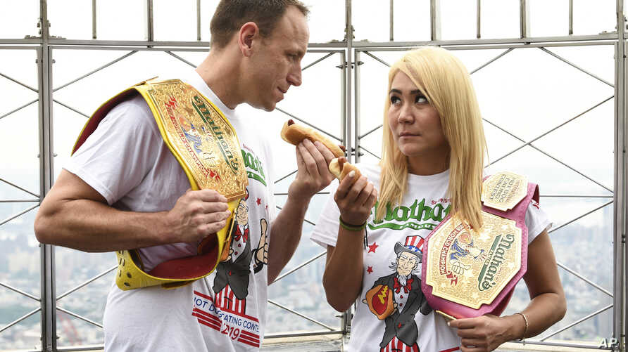 Eleven-time and defending men's champion Joey Chestnut, left, and defending women's champion Miki Sudo pose together during Nathan's Famous international Fourth of July hot dog eating contest weigh-in at the Empire State Building on Wednesday, July…
